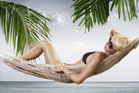 view of nice woman lounging in hammock in tropical environment Stock Photo - 6868314