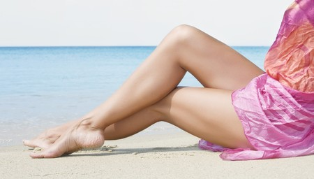 beach feet: close up view of nice smooth woman's legs on beach Stock Photo