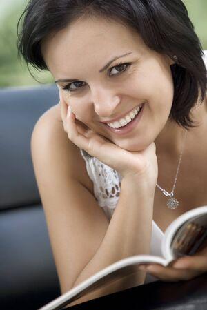 fresh news: portrait of young beautiful woman reading magazine  Stock Photo