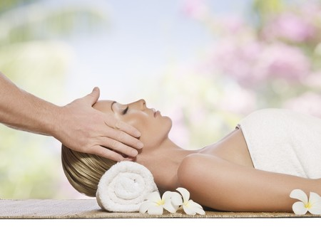facial massage: portrait of young beautiful woman in spa environment