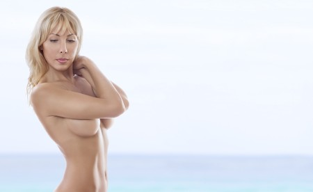 beach breast: High key portrait of young beautiful woman on color  back