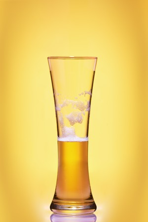 beerglass: close up view of filled beer glass on yellow background