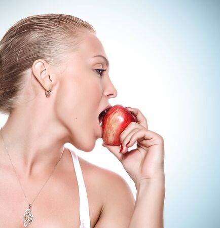 portrait of young beautiful woman biting apple on blue back photo