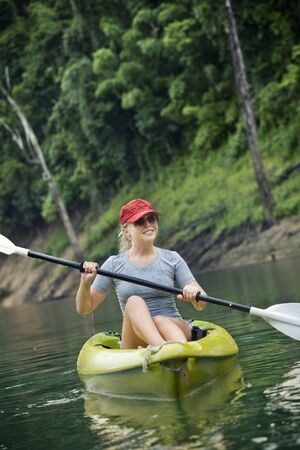 Portrait of nice young woman paddling kayak in summer  environment photo