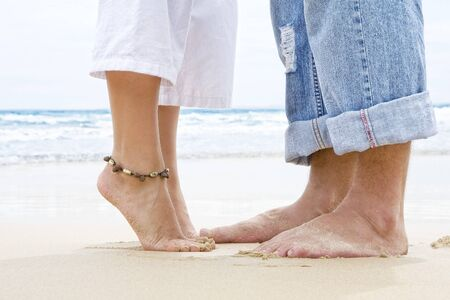 beach feet: Close up view of  pair of human's feet on sandy beach back