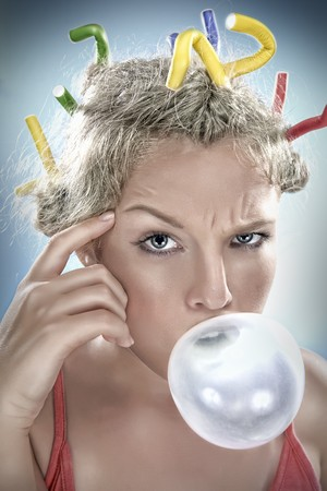 curler: Close up portrait of young girl blowing big bubble Stock Photo
