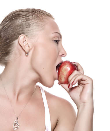 portrait of young beautiful woman biting apple on  white back photo