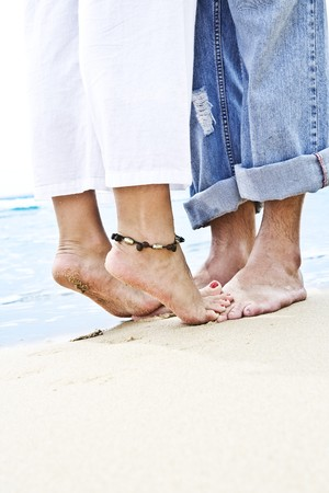 Close up view of  pair of human's feet on sandy beach back