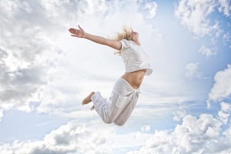 Portrait of young jumping woman on blue sky background photo