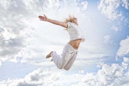 vida natural: Retrato de joven saltando a mujer sobre fondo de cielo azul  Foto de archivo