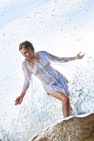 portrait of young beautiful water splashed  woman  on color  back