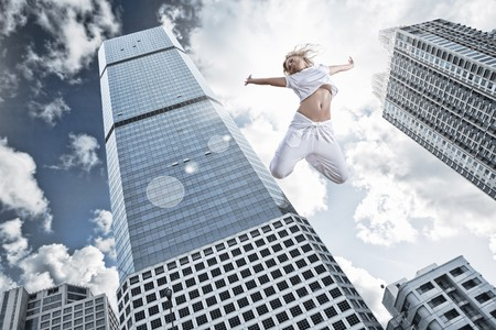fearless: Portrait of young jumping woman on blue sky background