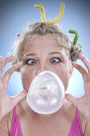 Portrait of young woman blowing bubble on color back photo
