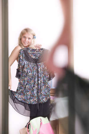 Portrait of young beautiful woman checking herself in mirror photo