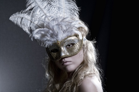 Close up portrait of young woman wearing mask on black  back photo