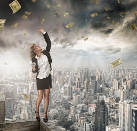 portrait of young woman catching money on color background photo