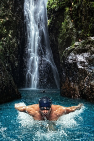 sportman: portrait of young man swimming in tropical waterfall