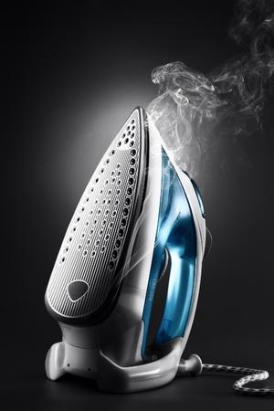 woman ironing: close up low key view of nice modern iron on black back