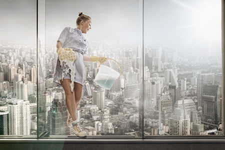 housekeeping: portrait of young hotel maid  washing glass on the big city background Stock Photo
