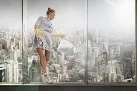 housekeeping: Retrato de sirvienta de hotel joven lavado de vidrio en el fondo de la gran ciudad