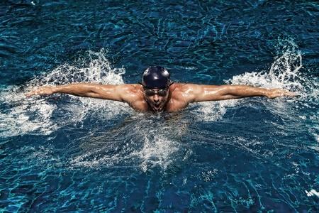 swim goggles: Retrato de hombre joven nadando en la piscina