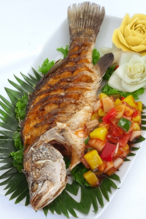 light meal: close up view of nice  fried fish with vegetables on white back