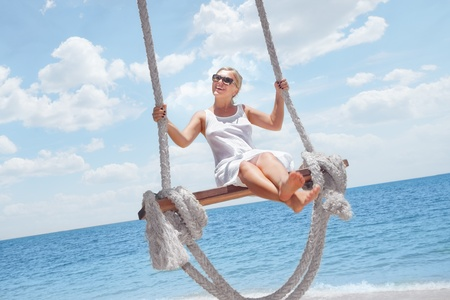 View of nice tropical  beach  with  girl on swing  photo