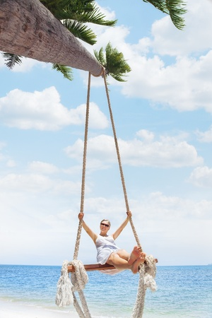 girl on swing: View of nice tropical  beach  with  girl on swing  Stock Photo