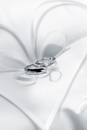 close up view of two wedding rings on white back photo