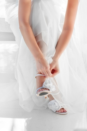 close up view of woman putting  some shoe on photo