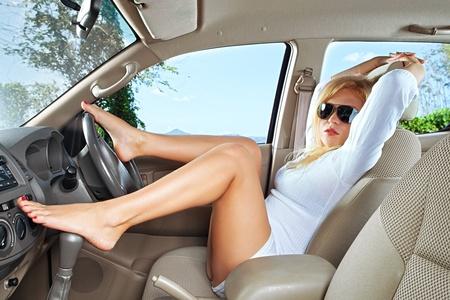 sexy füsse: Portrait der jungen schönen Frau sitzt im Auto Lizenzfreie Bilder