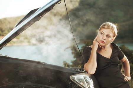 car trouble: portrait of young beautiful woman with broken car aside