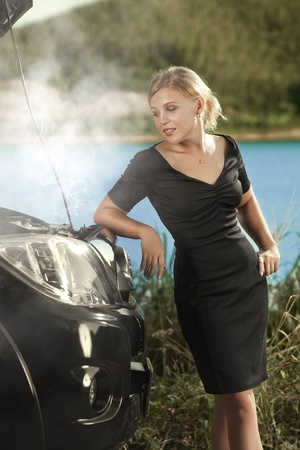 portrait of young beautiful woman with broken car aside photo