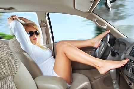 pies sexis: Retrato de joven bella mujer sentada en el coche Foto de archivo