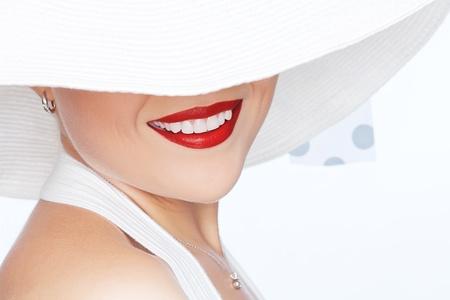 sonrisa: retrato de una mujer joven y hermosa en el sombrero sobre fondo blanco
