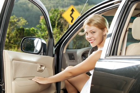 open car door: portrait of young beautiful woman sitting in the car