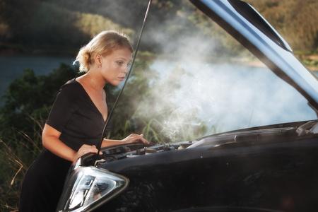 breakdown: portrait of young beautiful woman with broken car aside