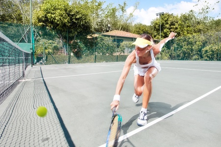 tennis court: portrait of young beautiful woman playing tennis in summer environment Stock Photo