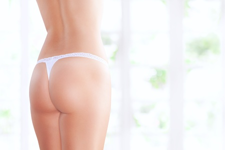 Close up view of nice smooth woman's butt on white back photo