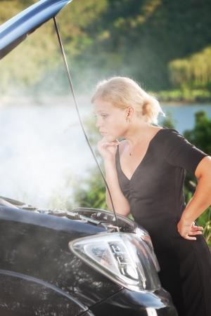 broken car: portrait of young beautiful woman with broken car aside