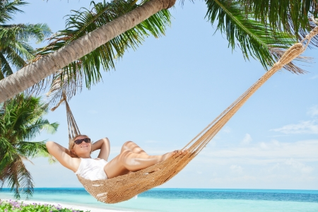 hammock: view of nice young lady swinging  in hummock on tropical beach Stock Photo