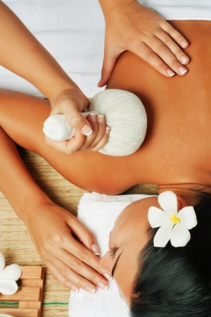 massage herbal: view of young beautiful woman in spa environment