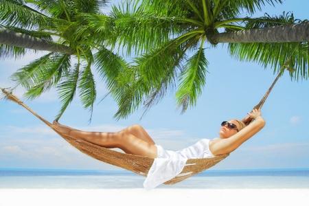 hamaca: ver de la se�ora joven agradable balanceo en loma en la playa tropical