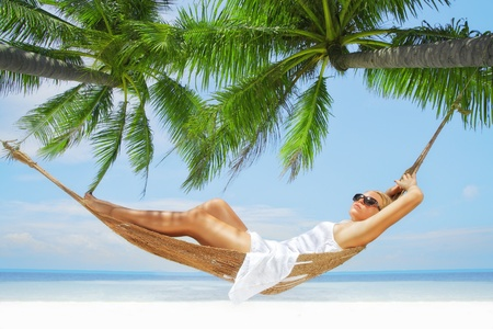 woman relaxing: view of nice young lady swinging  in hummock on tropical beach Stock Photo