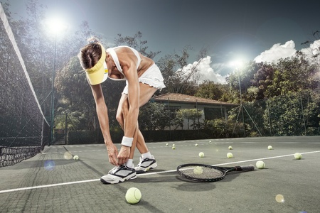 portrait of young beautiful woman playing tennis in summer environment Stock Photo