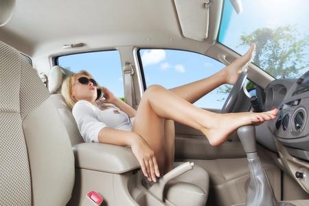 sexy f�sse: Portrait der jungen sch�nen Frau sitzt im Auto Lizenzfreie Bilder