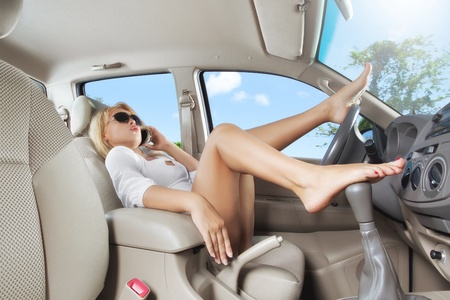 portrait of young beautiful woman sitting in the car photo