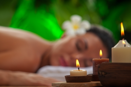 portrait of young beautiful woman in spa environment  blurred face, focused on candles Stock Photo - 13688851