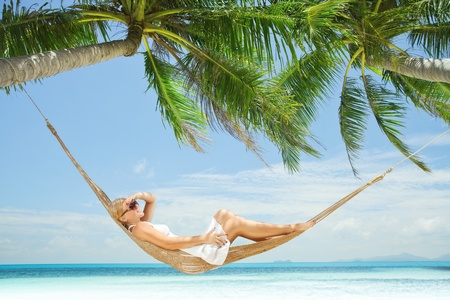 plage: view of nice young lady swinging  in hummock on tropical beach Stock Photo