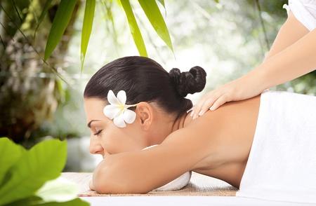 masaje corporal: retrato de una mujer joven y bella en el ambiente de spa